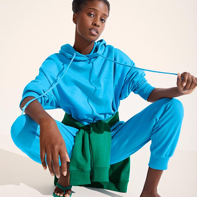 Mulher preta abaixada, olhando para a câmera, vestindo um conjunto de moletom hering azul com uma blusa verde amarrada na cintura e uma havaianas verde