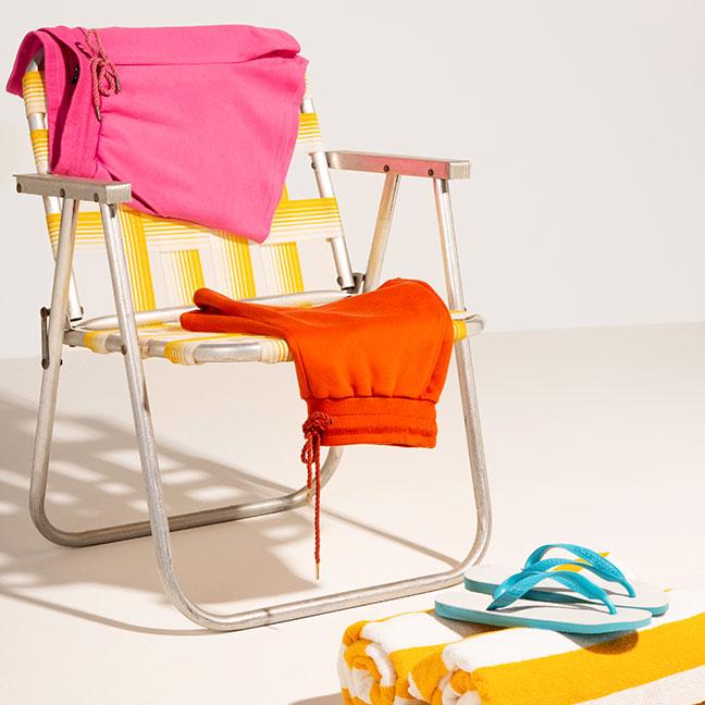 Cadeira de praia onde há dois shorts  Hering, um  rosa e outro azul.  No chão há uma toalha amarela e branca enrolada com um chinelo Havaianas em cima.