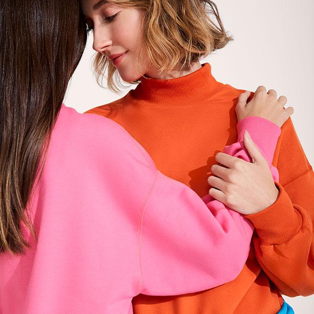 Duas mulheres abraçadas com as testas unidas , uma delas possui o cabelo castanho, está de costas e veste um moletom Hering rosa. A  outra possui o cabelo curto  e loiro e está de frente para  a câmera e veste um moletom laranja